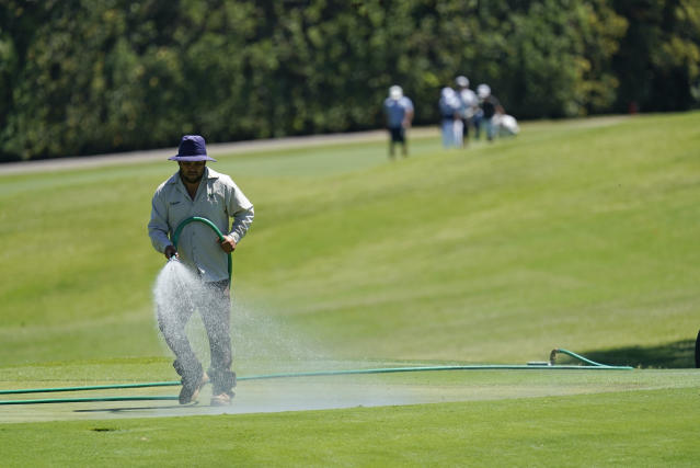 A greenskeeper sprays water onto the 12th green during practice for the Charles Schwab Challenge golf tournament at the Colonial Country Club in Fort Worth, Texas, Wednesday, June 10, 2020. (AP Photo/David J. Phillip)