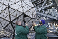 Workers install a panel of Waterford crystal triangles on the Times Square New Year's Eve ball, Sunday, Dec. 27, 2020, in New York, in preparation for a pandemic-limited celebration. (AP Photo/Kathy Willens)