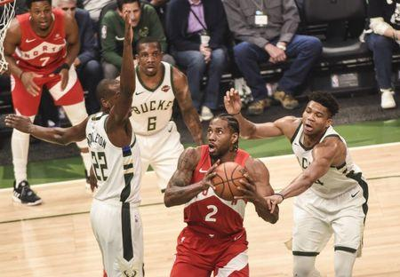 May 23, 2019; Milwaukee, WI, USA; Toronto Raptors forward Kawhi Leonard (2) controls the ball between Milwaukee Bucks forward Khris Middleton (22), guard Eric Bledsoe (6) and forward Giannis Antetokounmpo (34) in the first quarter in game five of the Eastern conference finals of the 2019 NBA Playoffs at Fiserv Forum. Mandatory Credit: Benny Sieu-USA TODAY Sports