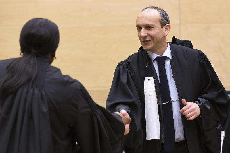 Emmanuel Altit, the defence counsel for former Ivory Coast President Laurent Gbagbo, right, shakes hands with International Criminal Court (ICC) prosecutor Fatou Bensouda, left, prior to the start of a confirmation of charges hearing at the ICC in The Hague, Netherlands, Tuesday Feb. 19, 2013. ICC prosecutors will begin laying out a summary of their evidence to allow judges to decide if it is strong enough to merit putting former Ivory Coast President Laurent Gbagbo on trial for crimes against humanity allegedly committed after disputed 2010 presidential elections. (AP Photo/Michael Kooren, Pool)