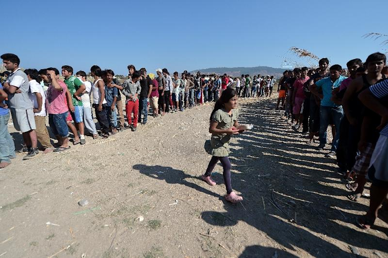 """Migrants queue to receive food during a distribution organized by the local organisation """"Kos solidarity"""" outside the abandoned Captain Elias hotel, where hundreds of migrants found temporary shelter in Kos, on August 17, 2015 (AFP Photo/Louisa Gouliamaki)"""