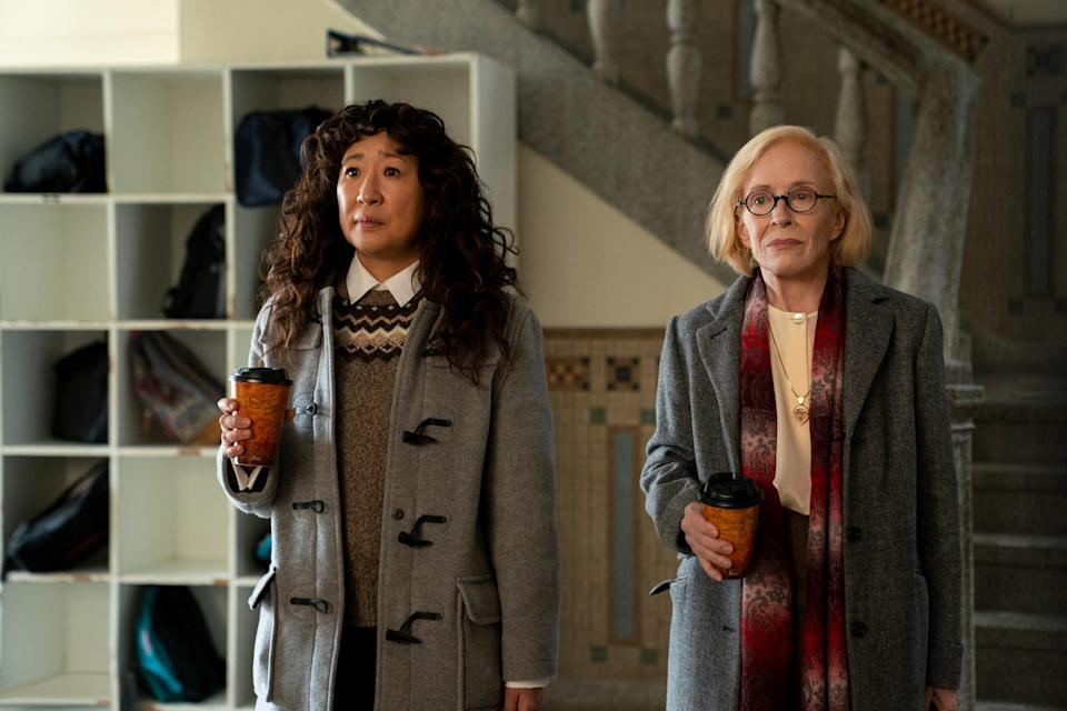 Photo of Sandra Oh and Taylor Holland in The Chair dressed in winter clothes, holding coffees