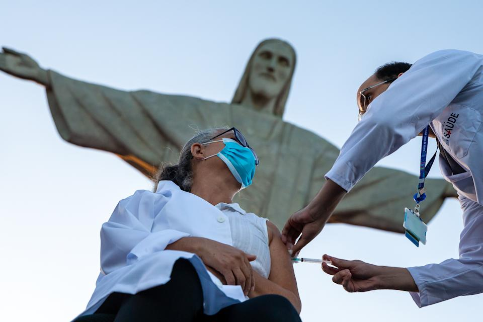 RIO DE JANEIRO, BRAZIL - JANUARY 18: Dulcinea da Silva Lopes, 59, receives the CoronaVac vaccination shot at the feet of the statue of Christ the Redeemer on January 18, 2021 in Rio de Janeiro, Brazil. Dulcinea is a nursing technician at Hospital Municipal Ronaldo Gazolla and has been working on the front lines of the fight against Covid-19 for 8 months. The state of Rio de Janeiro will immunize with the first vaccine shipment Health workers, institutionalized people aged 60 or over, Indigenous and quilombolas on their own land and institutionalized people with disabilities. The CoronaVac vaccine was developed by the Chinese laboratory Sinovac in partnership with the Butantan Institute. (Photo by Buda Mendes/Getty Images)
