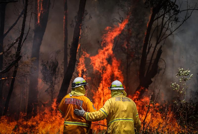 A NSW Rural Fire Service volunteer is given instructions by a colleague as he douses a fire during back-burning operations near Kulnura, NSW.