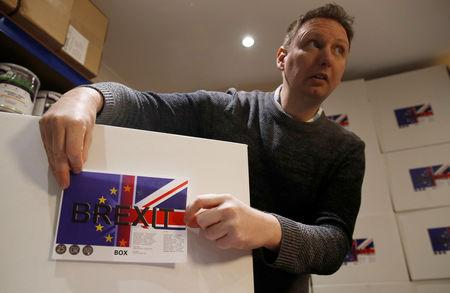 James Blake from emergency food storage.co.uk sticks a label on the company's 'Brexit Box' which contains dehydrated food, water purifying kit and fire starting gel at their warehouse in Leeds, Britain January 21, 2019.  REUTERS/Phil Noble