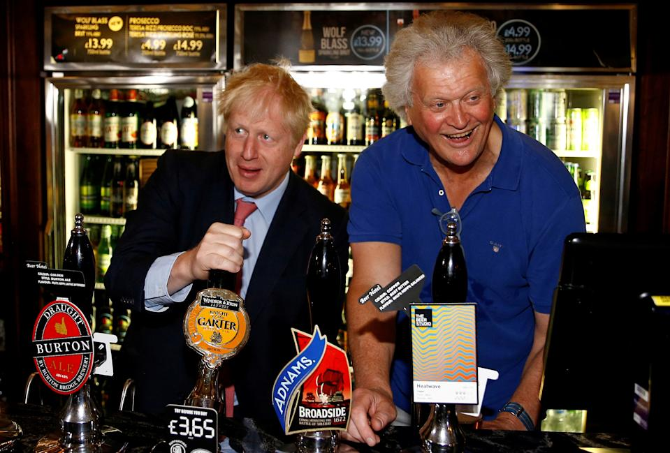 """Conservative leadership contender Boris Johnson (L) pulls a pint of Windsor & Eton brewery's """"Knight of the Garter"""" beer as he talks with JD Wetherspoon chairman Tim Martin during his visit to their Metropolitan Bar in London, on July 10, 2019. (Photo by HENRY NICHOLLS / POOL / AFP)        (Photo credit should read HENRY NICHOLLS/AFP via Getty Images)"""