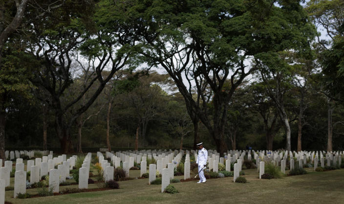 """FILE - In this Sunday, Nov. 13, 2016 file photo, a Kenyan naval officer pauses as he walks amongst the graves before observing Remembrance Sunday, to honor the contribution of those British and Commonwealth military who died in the two World Wars and later conflicts, at the Nairobi War Cemetery in Kenya. The Commonwealth War Graves Commission has apologized after an investigation found that at least 161,000 mostly Africans and Indians who died fighting for the British Empire during World War I weren't properly honored due to """"pervasive racism"""", according to findings released Thursday, April 22, 2021. (AP Photo/Ben Curtis, File)"""