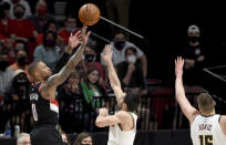Portland Trail Blazers guard Damian Lillard, left, hits a shot over Denver Nuggets guard Facundo Campazzo, center, and center Nikola Jokic, right, during the first half of Game 4 of an NBA basketball first-round playoff series in Portland, Ore., Saturday, May 29, 2021. (AP Photo/Steve Dykes)