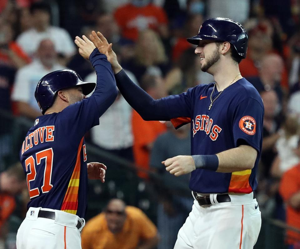 HOUSTON, TEXAS - OCTOBER 03: Kyle Tucker #30 of the Houston Astros receives a high five from Jose Altuve #27 after hitting a two run home run in the sixth inning against the Oakland Athletics at Minute Maid Park on October 03, 2021 in Houston, Texas. (Photo by Bob Levey/Getty Images)