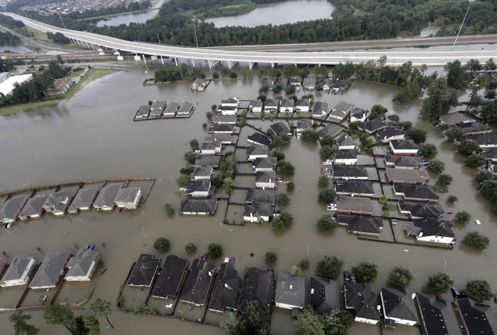 <p>Homes are surrounded by floodwaters from Tropical Storm Harvey Tuesday, Aug. 29, 2017, in Spring, Texas. (Photo: David J. Phillip/AP) </p>