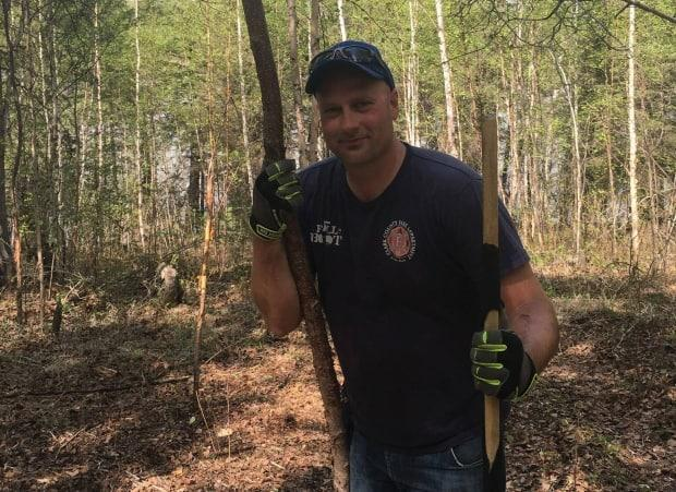 Jeff Reeder walks along the trail near the space where the organization he co-founded, River Valley Resilience Retreat, hopes to build a lodge for first responders and their families. (Submitted by Jeff Reeder - image credit)