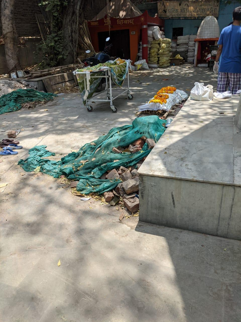 A dead body lying on the ground as over a dozen pyres burn inside the cremation ground during the second Covid waveStuti Mishra
