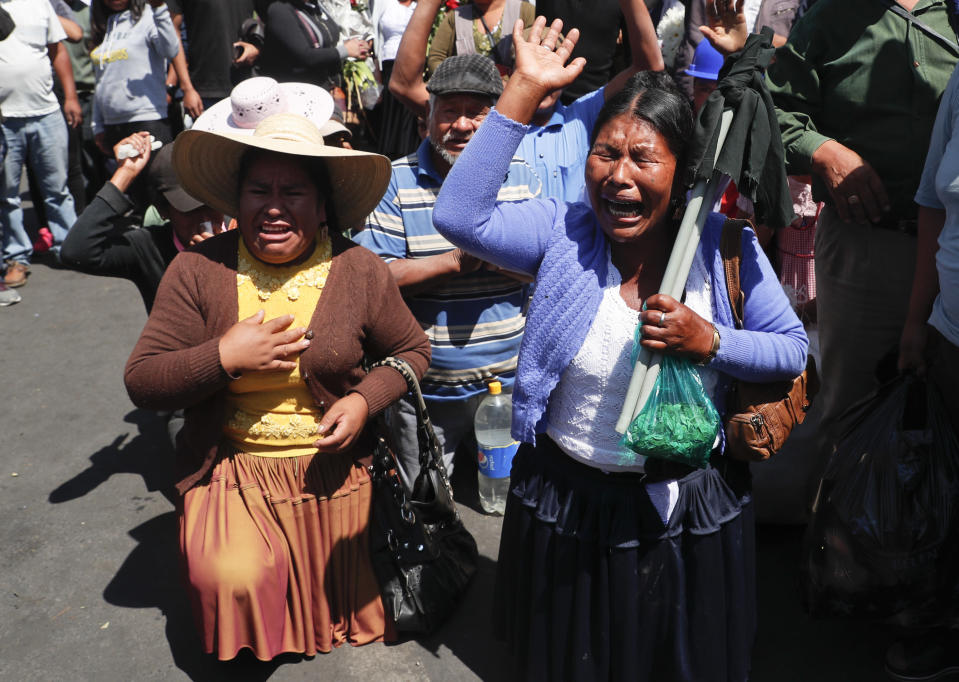 Coca growers kneel during a protest of backers of former President Evo Morales in Sacaba, Bolivia, Saturday, Nov. 16, 2019. Bolivia's political crisis turned deadly after security forces opened fire on Morales' supporters in Sacaba Friday, killing at least five people, injuring dozens and threatening the interim government's efforts to restore stability following the resignation of the former president in an election dispute. (AP Photo/Juan Karita)