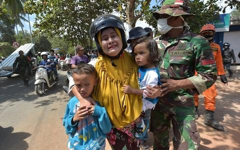 An Indonesian woman cries next to her children shortly after an aftershock hits the area in Tanjung on Lombok island on August 9 - Credit: ADEK BERRY/AFP