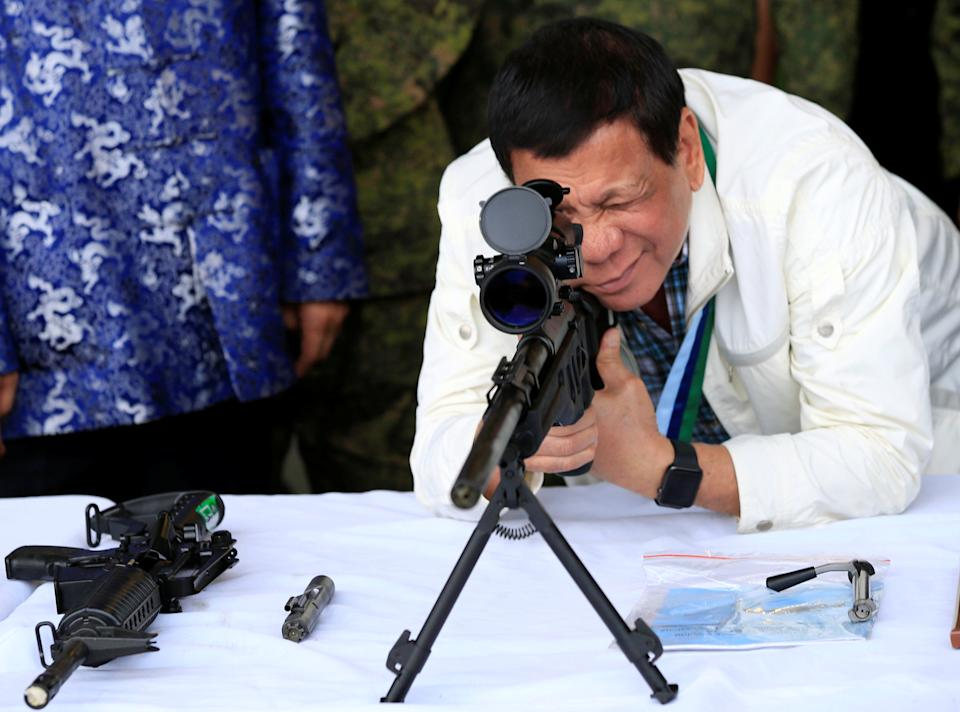 FILE PHOTO: President Rodrigo Duterte checks the scope of a 7.62mm sniper rifle during the turnover ceremony of China's urgent military assistance given