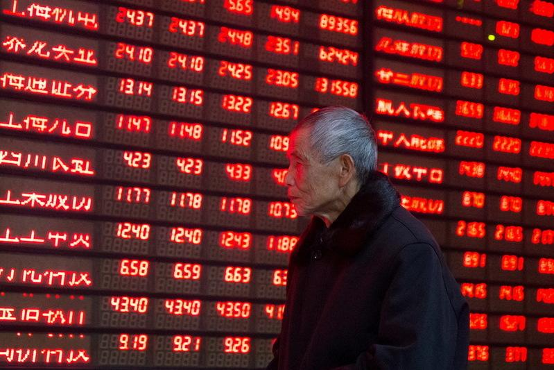An investor walks past an electronic screen showing stock information at a brokerage house in Nanjing
