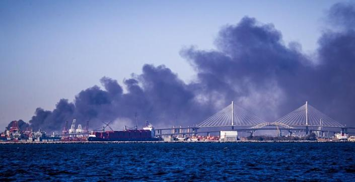Long Beach, CA - October 13 A large fire at a commercial yard in the Long Beach/Carson area sends thick black smoke into the air as viewed off the coast of Long Beach Wednesday, Oct. 13, 2021 in Long Beach, CA. (Allen J. Schaben / Los Angeles Times)