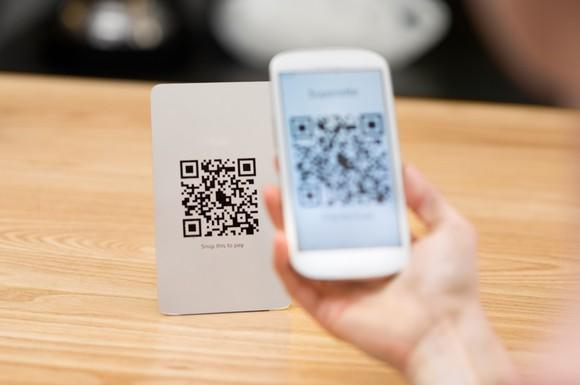 Shopper uses a merchant's displayed QR code to pay for a purchase.