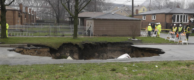 Officials survey a gaping sinkhole that opened up a residential street on Chicago's South Side after a cast iron water main dating back to 1915 broke during a massive rain storm, Thursday, April 18, 2013, in Chicago. The hole spanned the entire width of the road and chewed up grassy areas abutting the sidewalk. Two of the cars that disappeared inside had been parked, but a third was being driven when the road buckled and caved in. Only the hood of one of the vehicles can be seen peeking from the chasm.(AP Photo/M. Spencer Green)