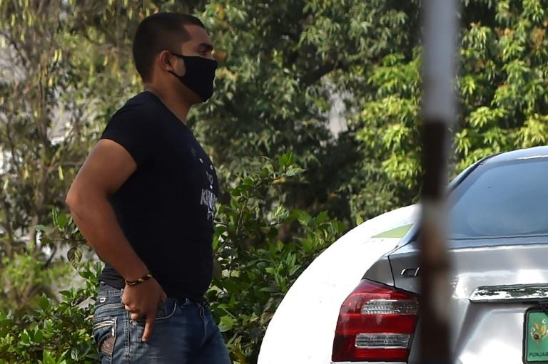 Pakistani cricketer Umar Akmal, wearing a face mask, was whisked away by his driver without speaking to the media in Lahore after a disciplinary hearing handed down his three-year ban