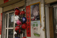 A poster showing a hand and slogans calling for all citizens to take action against evil cults is seen in front of a shop in Peyzawat County in northwestern China's Xinjiang Uyghur Autonomous Region on March 19, 2021. Pedestrians walk by statutes depicting Uyghurs in traditional garb dancing on a shopping street in Aksu, in China's far west Xinjiang region, on March 18, 2021. Four years after Beijing's brutal crackdown on largely Muslim minorities native to Xinjiang, Chinese authorities are dialing back the region's high-tech police state and stepping up tourism. But even as a sense of normality returns, fear remains, hidden but pervasive. (AP Photo/Ng Han Guan)