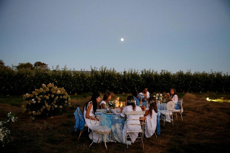"""""""The full moon rising over the reception and guests. Choosing the perfect outdoor evening required coordination with the full moon calendar in mind,"""" Dean says. """"We learned this from Nancy Hessel Weber, from the many full moon dinners and dance parties she's entertained at The Dining Shed. The full moon basks the entire field in light."""""""