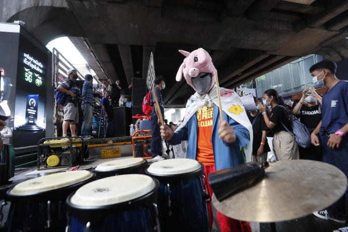 """An individual wearing a mask beats conga drums during a student rally in Bangkok, Saturday, Nov. 21, 2020. Organized by a group that mockingly calls themselves """"Bad Students,"""" the rally calls for educational reforms and also supports the broader pro-democracy movement's demands for constitutional change. (AP Photo/Sakchai Lalit)"""