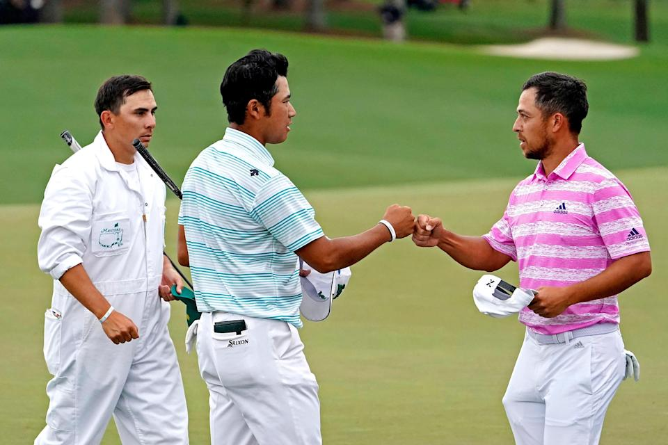 Hideki Matsuyama and Xander Schauffele fist-bump on the 18th green after completing their round Saturday at the Masters.
