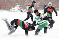 """Players compete for the ball during a """"snow rugby"""" tournament in a field after snowfall in Kabul on January 13, 2020. (Photo by WAKIL KOHSAR/AFP via Getty Images)"""