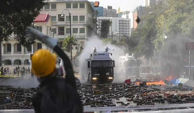 A protester hurls a brick at a police water cannon truck during clashes in Kowloon. Photo: Sam Tsang