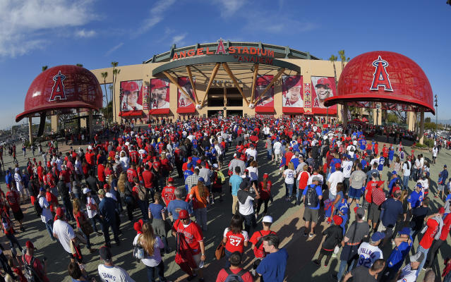 FILE - In this April 4, 2016, file photo, fans line up outside Angel Stadium of Anaheim for an opening day baseball game between the Los Angeles Angels and the Chicago Cubs, in Los Angeles. It used to be that empty seats caused palpitations in team owners and college administrators relying on ticket sales and concessions to beef up the profit margins. Now, those empty seats and short lines and clear concourses will be the norm for a while as sports grapples with social distancing requirements. (AP Photo/Mark J. Terrill)