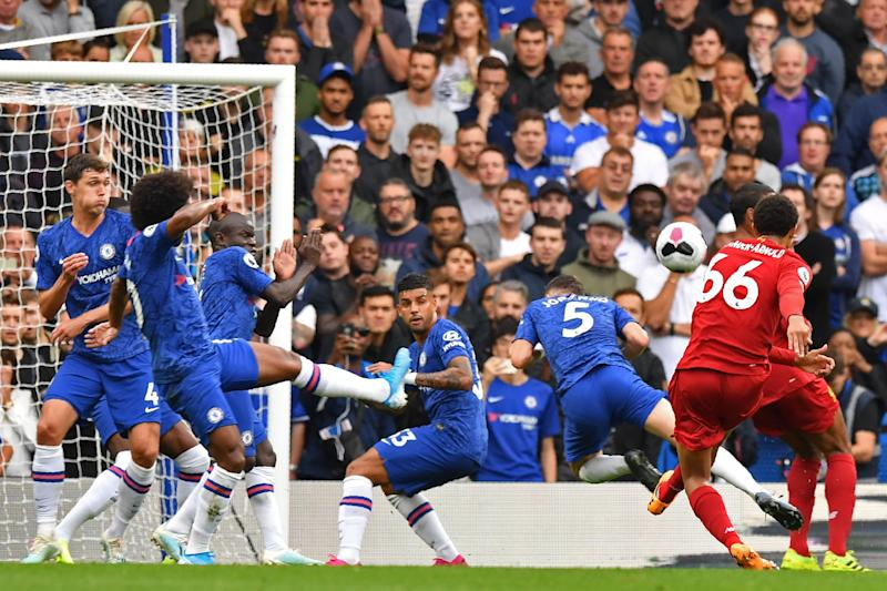Liverpool's English defender Trent Alexander-Arnold (R) shoots to score the opening goal during the English Premier League football match between Chelsea and Liverpool at Stamford Bridge in London on September 22, 2019. (Photo by OLLY GREENWOOD / AFP) / RESTRICTED TO EDITORIAL USE. No use with unauthorized audio, video, data, fixture lists, club/league logos or 'live' services. Online in-match use limited to 120 images. An additional 40 images may be used in extra time. No video emulation. Social media in-match use limited to 120 images. An additional 40 images may be used in extra time. No use in betting publications, games or single club/league/player publications. / (Photo credit should read OLLY GREENWOOD/AFP/Getty Images)