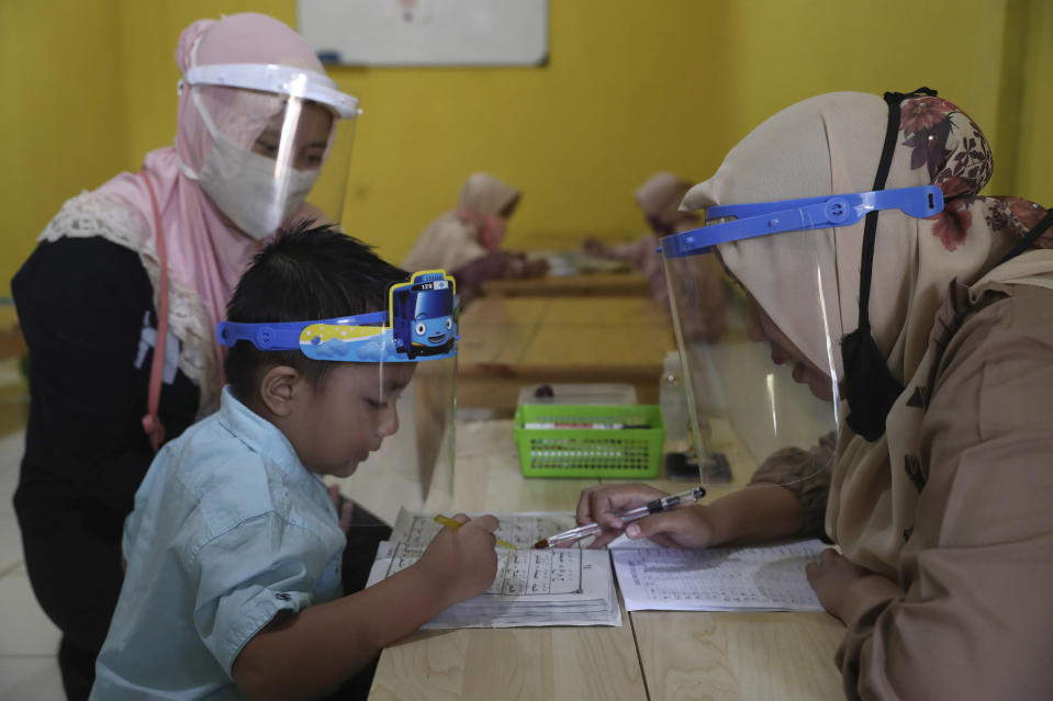 Teachers and students wear protective gear as a precaution against the new coronavirus outbreak during a class at a Quran educational facility at on the outskirts of Jakarta, Indonesia, Wednesday, July 1, 2020. The government of Indonesia's capital region is extending the first transition phase from large-scale social restrictions in Jakarta as the number of new confirmed coronavirus cases continues to rise. (AP Photo/Tatan Syuflana)