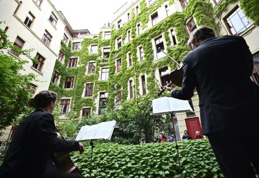 Members of the Staatskapelle Berlin orchestra tune up for a short concert in the courtyard of an apartment building in Berlin