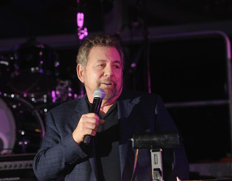 James Dolan in a suit jacket with a microphone at an event.