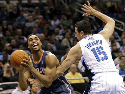 Charlotte Bobcats' Gerald Henderson, left, attempts a shot while being fouled by Orlando Magic's Hedo Turkoglu (15), of Turkey, during the first half of an NBA basketball game, Tuesday, Jan. 17, 2012, in Orlando, Fla. (AP Photo/John Raoux)