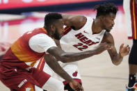 Miami Heat forward Jimmy Butler, right, pursues a loose ball with Denver Nuggets forward JaMychal Green in the first half of an NBA basketball game Wednesday, April 14, 2021, in Denver. (AP Photo/David Zalubowski)