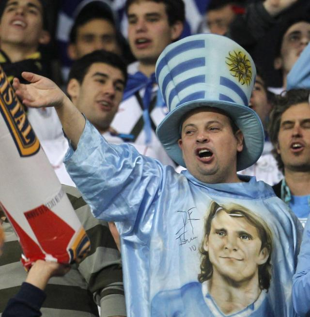 A Uruguay fan wearing a shirt with the image of of striker Diego Forlan, cheers during their 2014 World Cup qualifying soccer match against Peru in Lima, September 6, 2013. REUTERS/Enrique Castro-Mendivil (PERU - Tags: SPORT SOCCER)