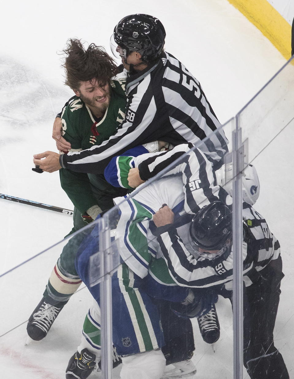 Minnesota Wild's Ryan Hartman (38) and Vancouver Canucks' J.T. Miller (9) fight during second-period NHL hockey game action in Edmonton, Alberta, Thursday, Aug. 6, 2020. (Jason Franson/The Canadian Press via AP)