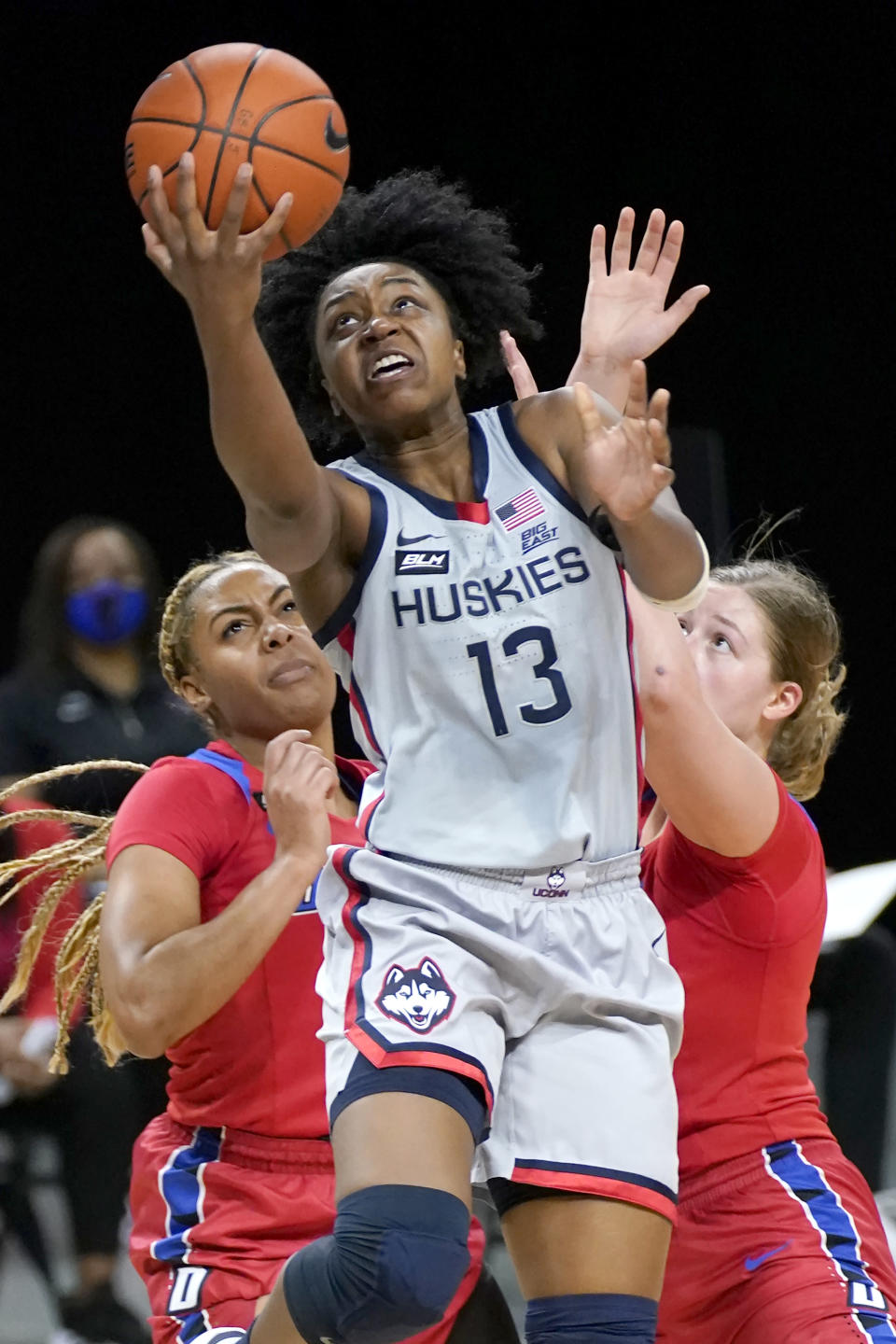 Connecticut's Christyn Williams (13) scores past DePaul's Deja Church, left, and Evina Westbrook during the first half of an NCAA college basketball game Sunday, Jan. 31, 2021, in Chicago. (AP Photo/Charles Rex Arbogast)