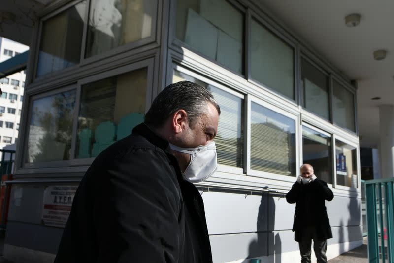 People wearing protective face masks sit outside the AHEPA hospital, where the first confirmed coronavirus case is being treated, in Thessaloniki