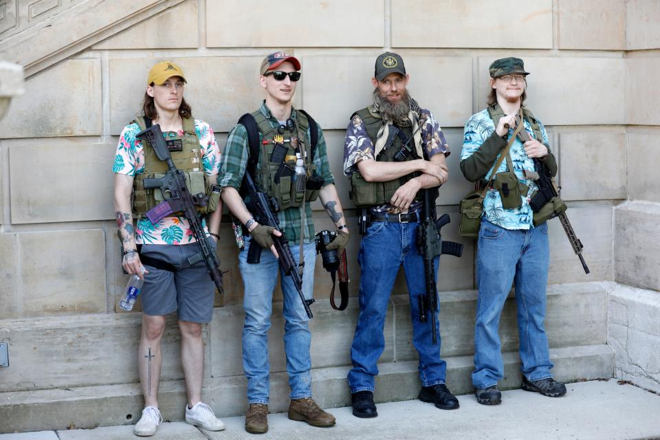 "Armed protesters take part in ""Operation Haircut,"" organized by the Michigan Conservative Coalition in opposition to mandatory lockdown measures to curtail the coronavirus pandemic, outside the Michigan State Capitol in Lansing, Mich. on May 20, 2020. The Hawaiian shirts are a kind of uniform for members of the extremist boogaloo movement.  (Jeff Kowalsky/AFP via Getty Images)"