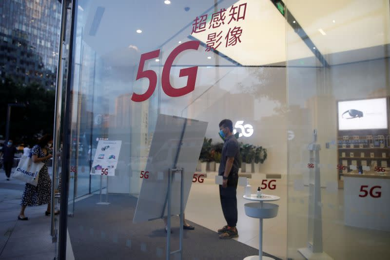 A woman wearing a face mask enters a Huawei store with 5G signs at a shopping mall, in Beijing