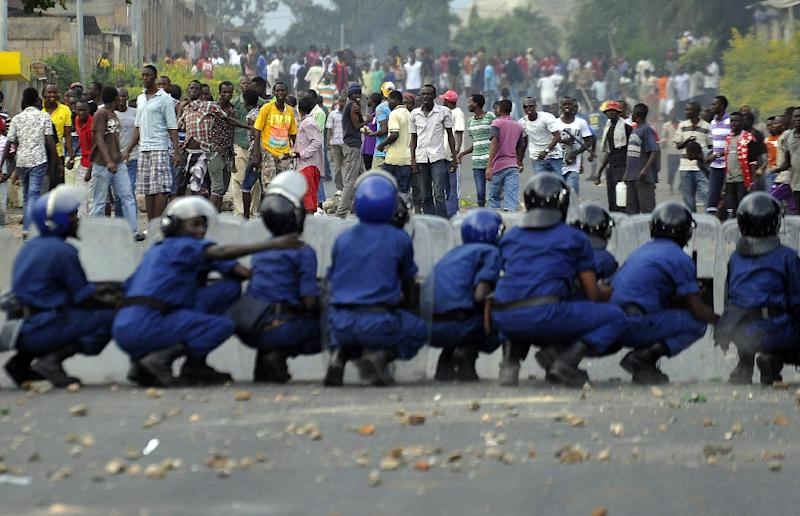 Burundian riot police form a barricade to hold protesters back during a demonstration against the president's bid to cling to power for a third term in Musaga, outskirts of Bujumbura, on April 28, 2015