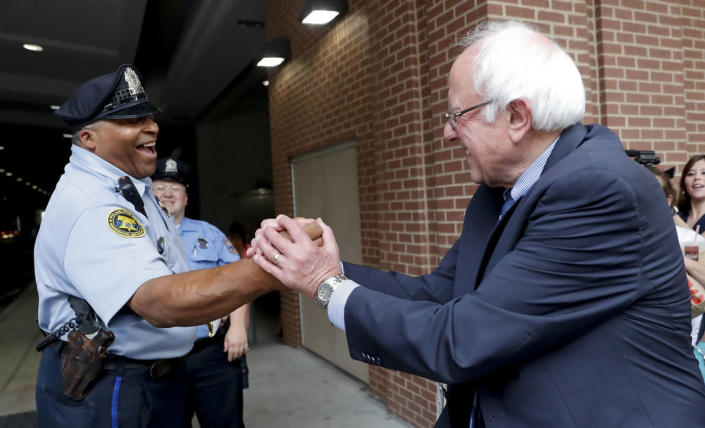 <p>Sen. Bernie Sanders, I-Vt., right, greets a police officer during walk around downtown in Philadelphia, July 28, 2016, during the final day of the Democratic National Convention. (Photo: John Minchillo/AP)</p>