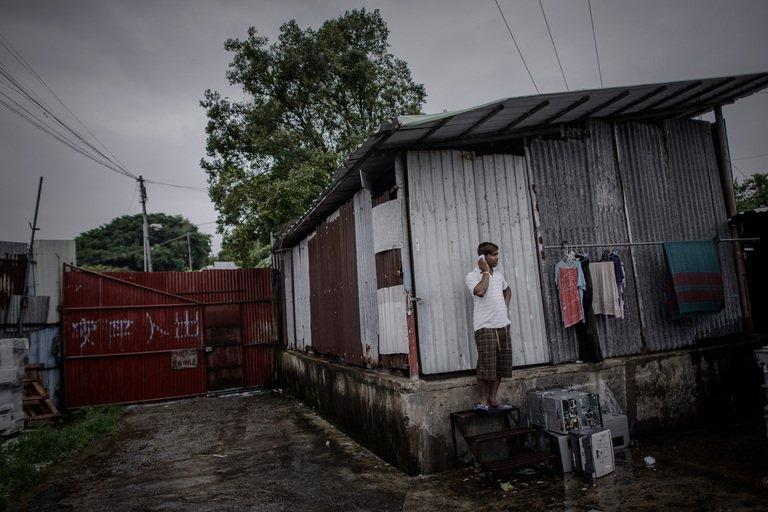 A refugee from Bangladesh using a mobile phone in the Ping Che district of Hong Kong, on June 11, 2013
