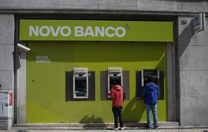People use ATM machines at a Novo Banco branch in downtown Lisbon,
