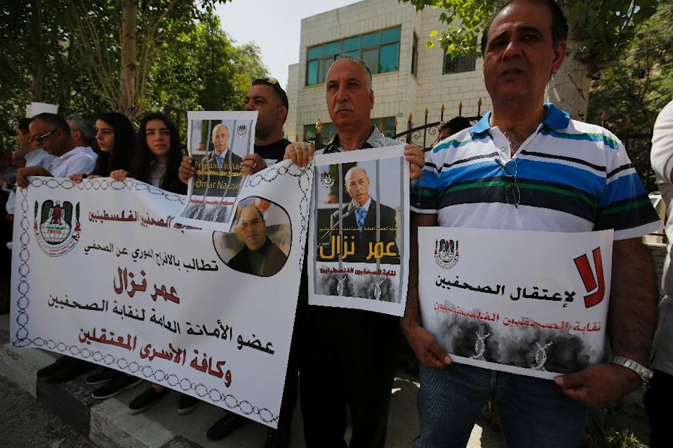 Palestinian journalists hold placards and banners during a demonstration on April 24, 2016 outside the Red Cross offices in the West Bank city of Ramallah in support of their detained colleague Omar Nazza (AFP Photo/Abbas Momani)