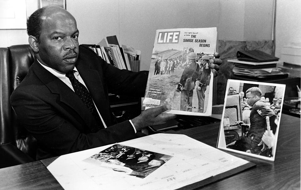 Atlanta City Councilman John Lewis holds the March 1965 issue of Life Magazine in his office in Atlanta, Ga., Aug. 7, 1986. The cover photo shows Lewis leading the first Selma, Ala., civil rights march with Hosea Williams. Lewis, an Alabama sharecropper's son, suffered brutal beatings and humiliating sentences in the five years preceding the Voting Rights Act. (Photo: Ric Feld/AP)