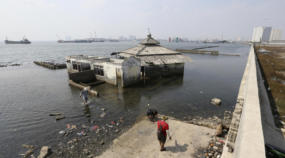 People walk near a giant sea wall which is used as a barrier to prevent sea water from flowing into land and cause flooding in Jakarta, Indonesia, Saturday, July 27, 2019. Indonesia's President Joko Widodo said in an interview that he wants to see the speedy construction of the giant sea wall to save the low-lying capital of Jakarta from sinking under the sea, giving renewed backing to a long-delayed multi-billion-dollar mega project. (AP Photo/Achmad Ibrahim)